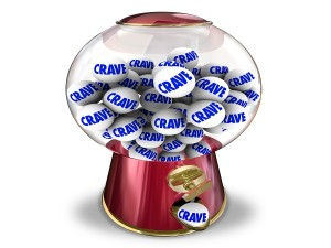 Crave word on gum balls in a candy machine or snack dispenser to illustrate a craving, appetite or hunger for sweets or junk food